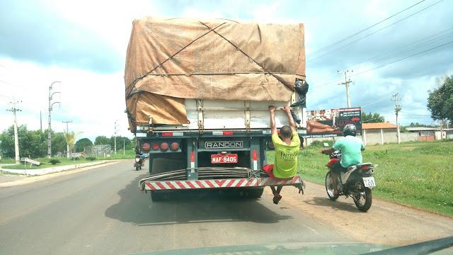 Homens viajam agarrados em caminhões na BR 316, próximo à Bacabal-MA